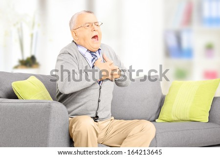 Senior man seated on a sofa having a heart attack at home - stock photo