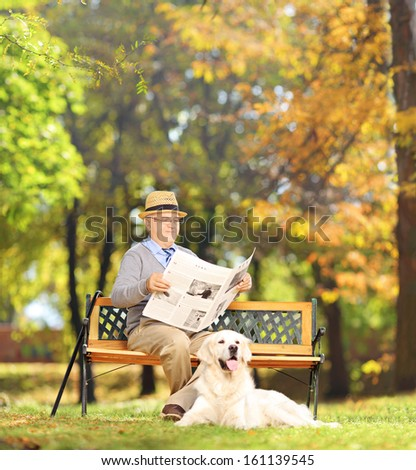 Senior man seated on a wooden bench reading a newspaper with his dog, in a park, shot with a tilt and shift lens - stock photo