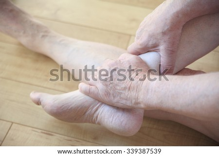 Senior man seated on floor holds an ankle with both hands. - stock photo