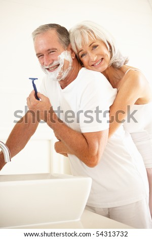 Senior Man Shaving In Bathroom Mirror With Wife Watching