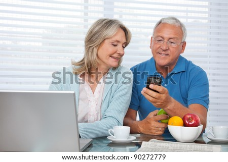 Senior man showing mobile phone to female - stock photo