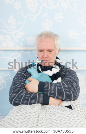 Senior man sick in bed with hot water bottle and thermometer - stock photo