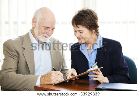 Senior man signing a contract while his broker looks on. - stock photo