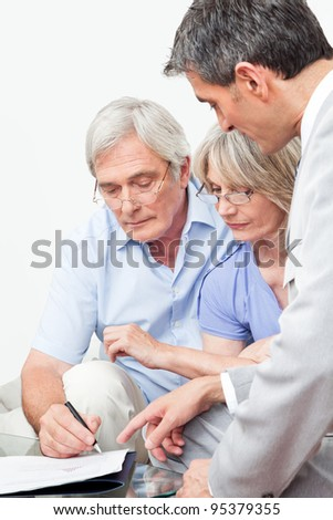 Senior man signing contract with financial advisor at home - stock photo