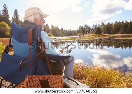 Senior man sits fishing in a lake, back view close-up - stock photo