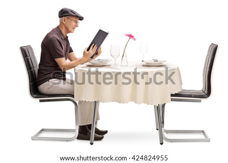 Senior man sitting at a restaurant table and looking at the menu isolated on white background - stock photo