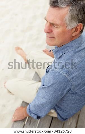 Senior man sitting by beach - stock photo