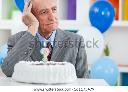 Senior man sitting front of birthday cake and trying to remember how old is - stock photo