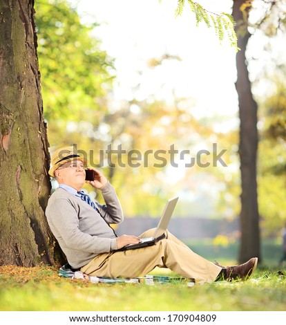 Senior man sitting in a park, talking on a cell phone and working on a laptop, shot with a tilt and shift lens - stock photo