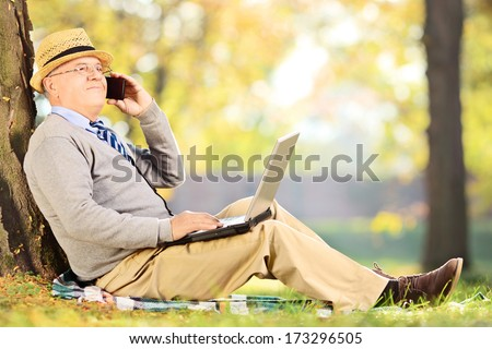 Senior man sitting in a park, talking on a mobile phone and working on a laptop - stock photo