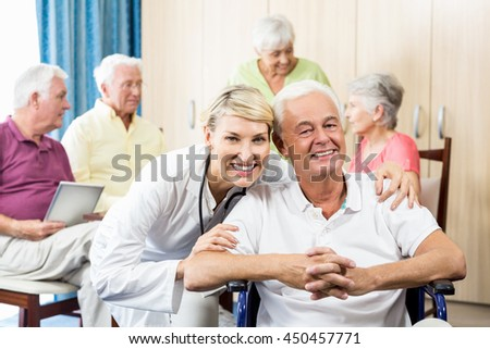 Senior man sitting in a wheelchair in a retirement home - stock photo