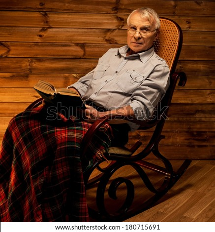 senior-man-sitting-in-rocking-chair-in-homely-wooden-interior-with-old ...