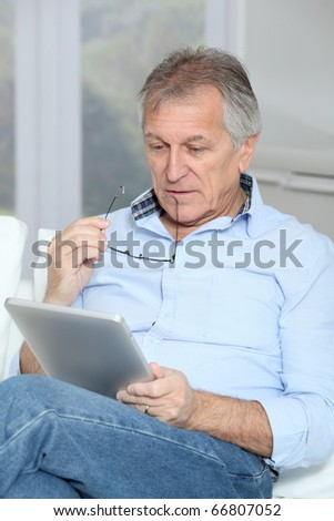 Senior man sitting in sofa with electronic tablet - stock photo