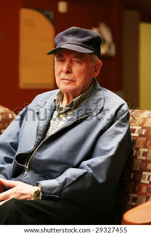 Senior man sitting in waiting room of hospital - stock photo