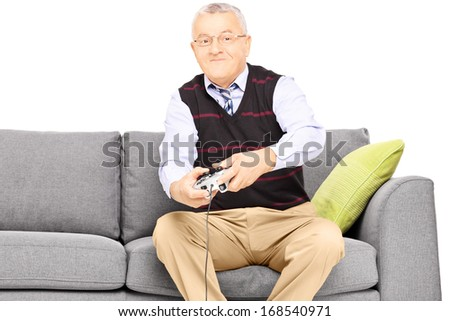 Senior man sitting on a sofa and playing video game isolated on white background - stock photo
