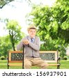 Senior man sitting on a wooden bench and looking at camera, in a park, shot with a tilt and shift lens - stock photo