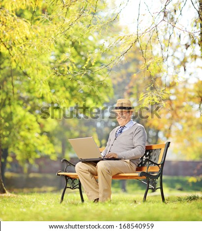 Senior man sitting on a wooden bench and working on a laptop in a park, shot with a tilt and shift - stock photo