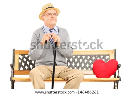 Senior man sitting on a wooden bench with red heart next to him, isolated against white background - stock photo