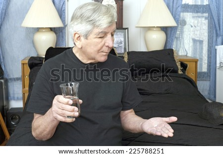 Senior man sitting on bed ready to take medication with water. He is of Puerto Rican ethnicity. - stock photo