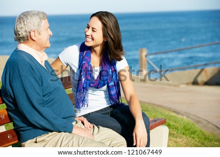 Senior Man Sitting On Bench With Adult Daughter By Sea - stock photo