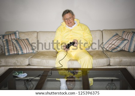 Senior man sitting on couch in tracksuit and playing video game - stock photo