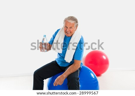 senior man sitting on fitness ball in gym and holding water bottle. Copy space