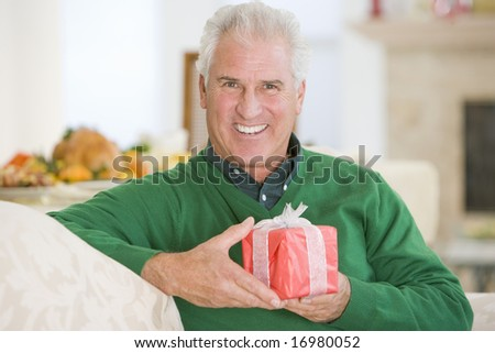 Senior Man Sitting On Sofa Holding A Christmas Gift - stock photo