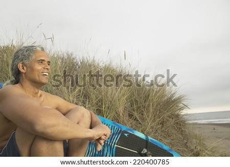 Senior man sitting on the dunes with a surfboard - stock photo