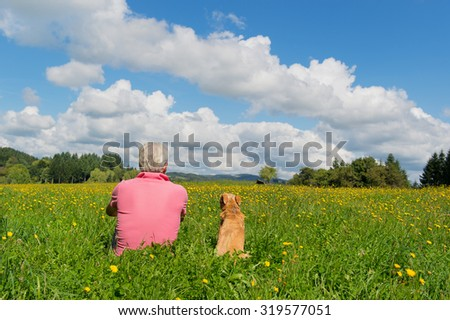 Senior man sitting with dog in landscape - stock photo