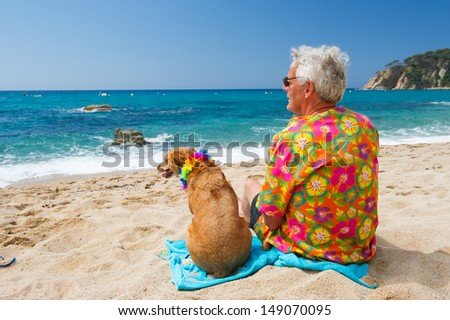 Senior man sitting with dog on tropical beach - stock photo