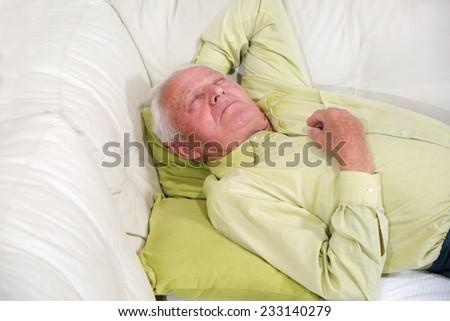 Senior man sleeping on sofa indoors - stock photo