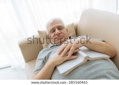 Senior man sleeping on sofa with a book - stock photo