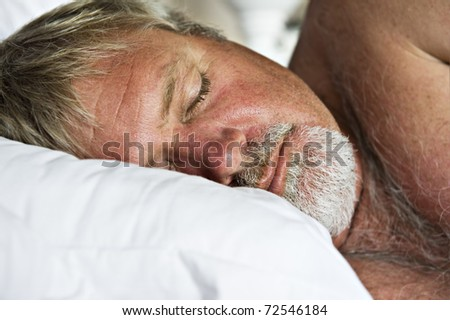 Senior man sleeping peacefully - intentional low light and shallow depth of field - stock photo