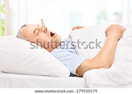 Senior man sleeping with a clothespin on his nose and snoring at home - stock photo