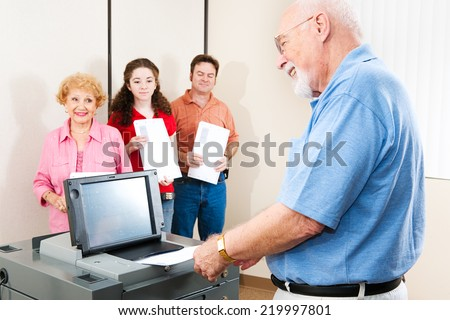 Senior man smiles as he casts his ballot on a new electronic voting machine.   - stock photo