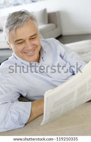 Senior man smiling as reading the newspaper - stock photo