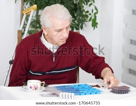 Senior man sorting his drugs in blue plastic pill container