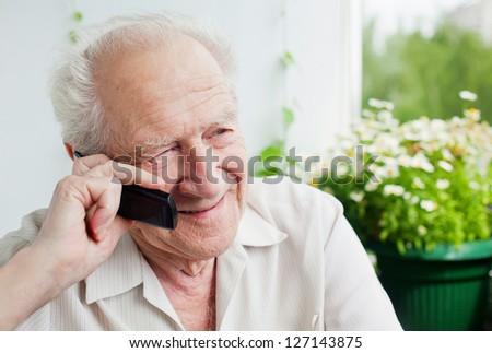 senior man speaking on the phone, enjoying a conversation with somebody - stock photo