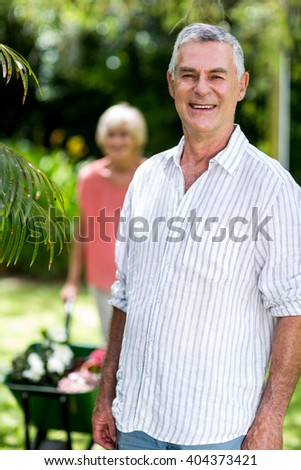 Senior man standing against woman with wheelbarrow at yard - stock photo