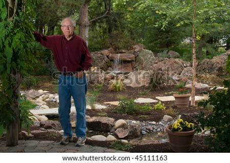 Senior man standing by a man-made pond and waterfall