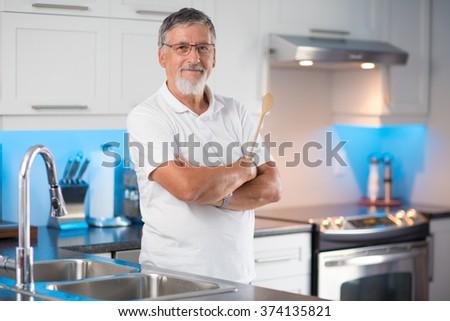 Senior man standing in his renovated, modern kitchen, - stock photo