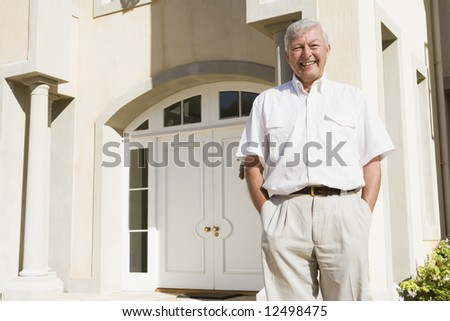 Senior man standing outside front door of house - stock photo