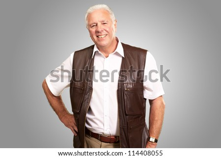 Senior Man Standing With Hand On Hips On Gray Background - stock photo