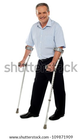 Senior man standing with the help of crutches. Recovering from an accident