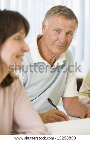 Senior man studying with other adult students - stock photo