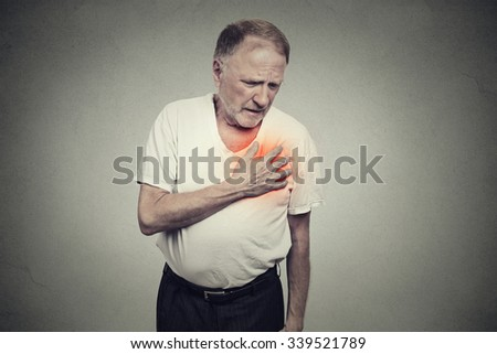 senior man suffering from bad pain in his chest heart attack isolated on gray background - stock photo