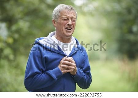 Senior Man Suffering Heart Attack Whilst Jogging - stock photo