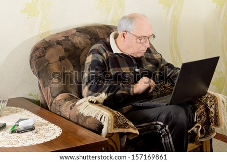 Senior man surfing the internet as he sits in a comfortable armchair in his living room with his laptop computer balanced on his lap - stock photo