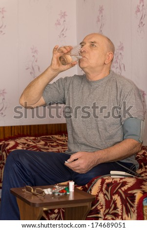 Senior man swallowing down his medication as he sits at a small table with an assortment of tablets and pills - stock photo
