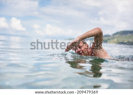 Senior man swimming in the Sea/Ocean - enjoying active retirement, having fun, taking care of himself, staying fit - stock photo